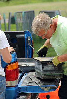 Mark Trout, right, the president of the Missouri Civil War Museum, examines a time capsule that was stowed for more than a century at the base of St. Louis' Confederate monument.