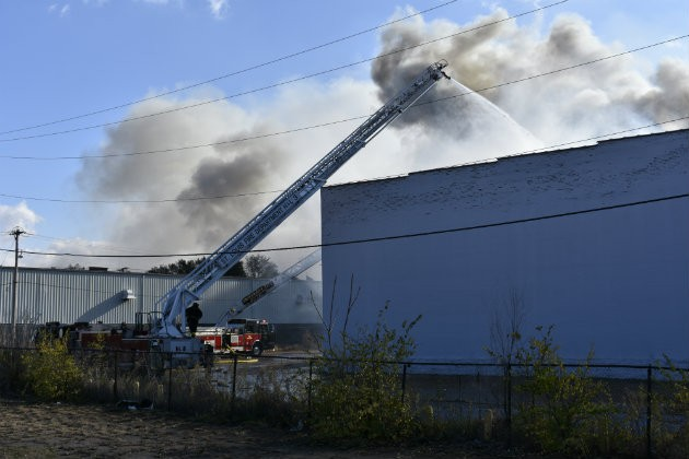 Firefighters pour water on warehouse fire in Botanical Heights. - PHOTO BY DOYLE MURPHY