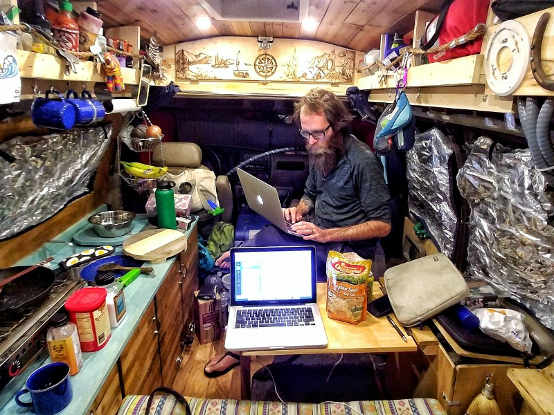 John Serbell works on his laptop after preparing a meal in the van's miniature kitchen. - COURTESY OF JOHN AND JAYME SERBELL
