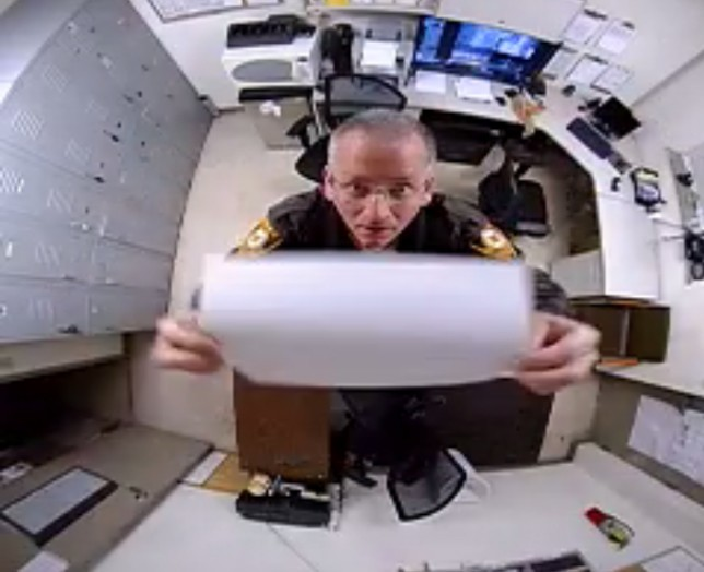 A St. Louis County police officer is shown covering up a surveillance camera in 2015. - IMAGE VIA METRO