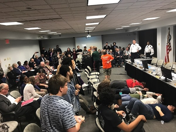 Students lie down in protest at a board of trustees meeting on November 30. - JON ALEXANDER