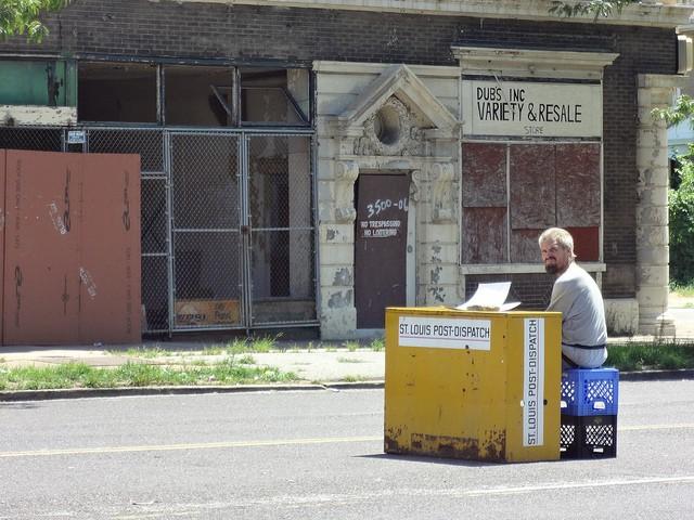 A newspaper vendor hawks his wares on North Grand. - FLICKR/PAUL SABLEMAN
