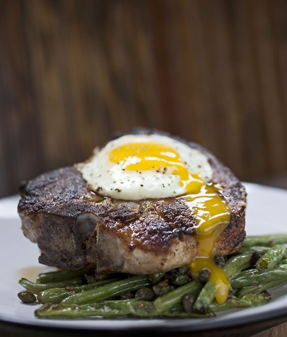 The Berkshire Pork Porterhouse is a Rensing's Porterhouse pork chop, sharp cheddar jalapeno bread pudding, green beans, and a sunny side up egg.