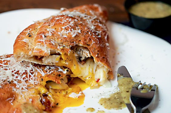 """The """"Which Came First...?"""" calzone is filled with roasted chicken, applewood-smoked bacon, jalapeños, egg, onion and mozzarella. It's served with a salsa verde. Slideshow: Sauce on the Side photos."""