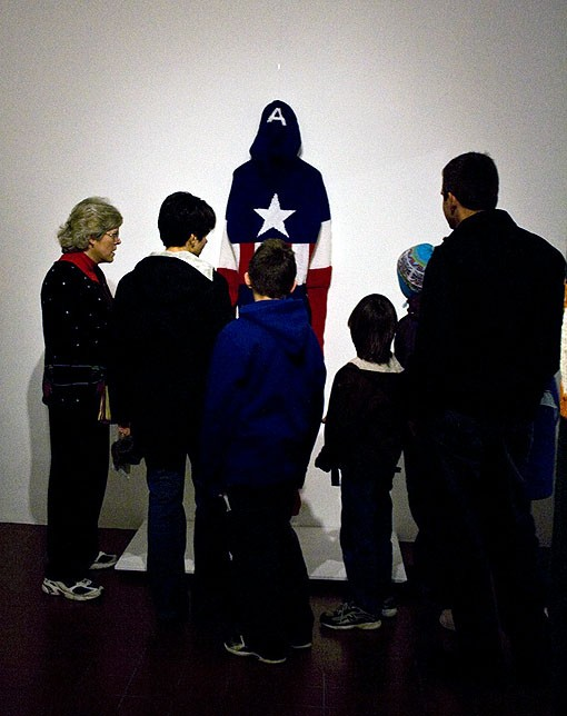 A family gathers around the costume of Captain America to take in the figure of the superhero. - PHOTO: EMILY GOOD
