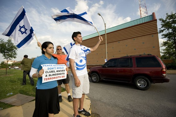 Supporters of Israel stand at a median across from Senator McCaskill's office while cars pass on Delmar during rush hour.