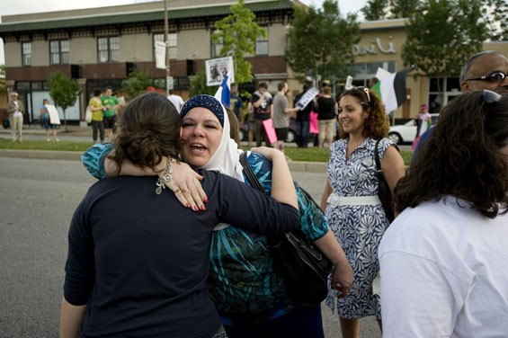 Zehra Sarim of St. Louis embraces protesters from the other side.