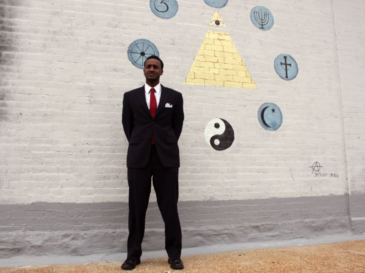 Abdul Kadir Mohamed stands in front of a mural on the side of his office building. He specializes in immigration cases. - DANNY WICENTOWSKI