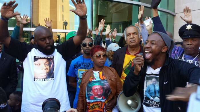 Michael Brown Sr., Lesley McSpadden and Pastor Carlton Lee in front of the Buzz Westfall Justice Center in Clayton Saturday. - JESSICA LUSSENHOP