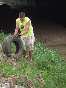 Greg Katski rolls a tire out of a runoff ditch in Columbia, Indiana. - LILY BERMAN