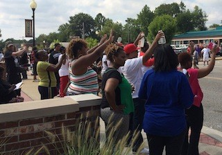 Protesters stand on the side of South Florissant Road outside the Ferguson Police Department.
