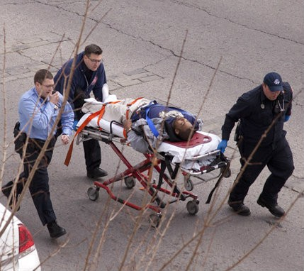 The alleged gunman is wheeled to an ambulance today at roughly 2:20 p.m. - JOSH ROWAN