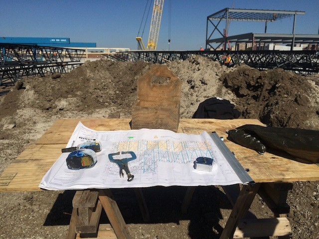 Blueprints and tools and stuff with the newly erected steel frame in the background. - MITCH RYALS