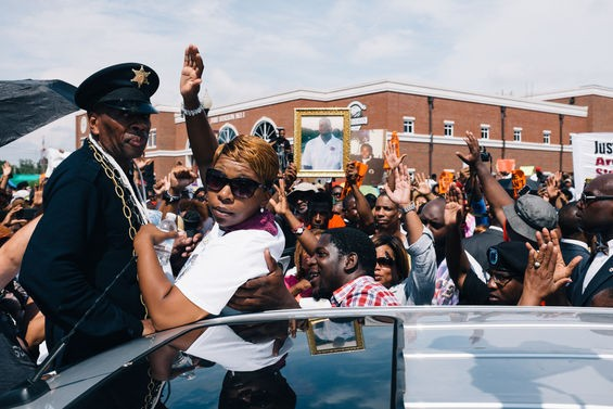 """Lesley McSpadden, Michael Brown's mother, throws up the """"Hands Up, Don't Shoot"""" sign at the Ferguson Police station. - ALL PHOTOS BY BRYAN SUTTER"""