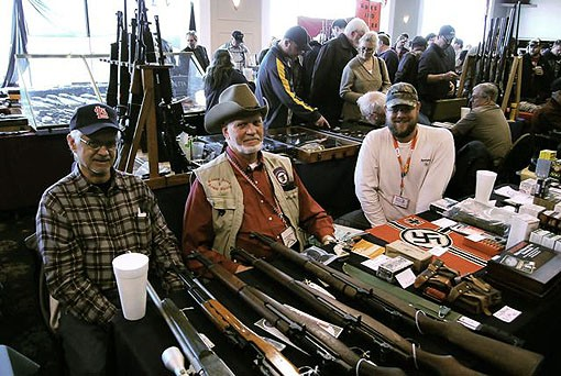 Alan Fasoldt (center) and father-son team Dominic Sr. (Left) and Dominic Jr. (Right) smile behind their collection of M1 Garands, ammo and war memorabilia. - PHOTO: MATT BLICKENSTAFF