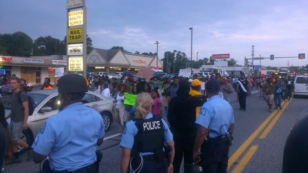 Protesters march in Ferguson as police guard stores. - RAY DOWNS
