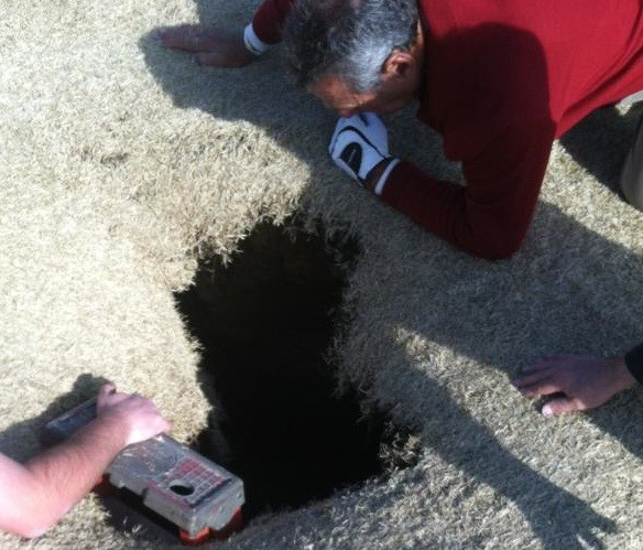 This sinkhole swallowed a golfer. - COURTESY OF GOLFMANNA.COM