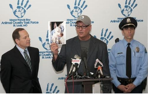 During a 2012 press conference, Randy Grim (center) holds up a photo of a dog that had been starved and thrown in a dumpster. - STRAY RESCUE