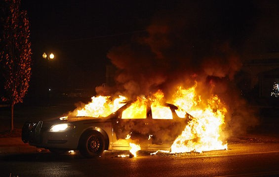 A police car burns.