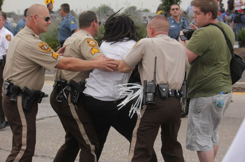 Minutes after this arrest, the man to the right (in green) was arrested while crossing the street. - DANNY WICENTOWSKI