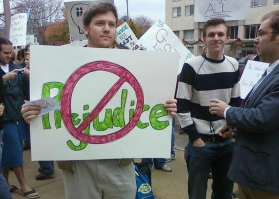 Burns (with sign), O'Keefe in striped shirt and fellow activist Joseph Basel (suit) sabotage a gay-right rally in St. Louis last November.