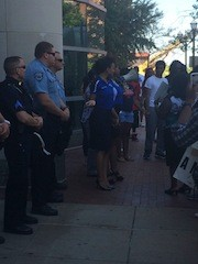 Protester extends a hand in prayer to a Clayton police officer. - PHOTO BY MITCH RYALS