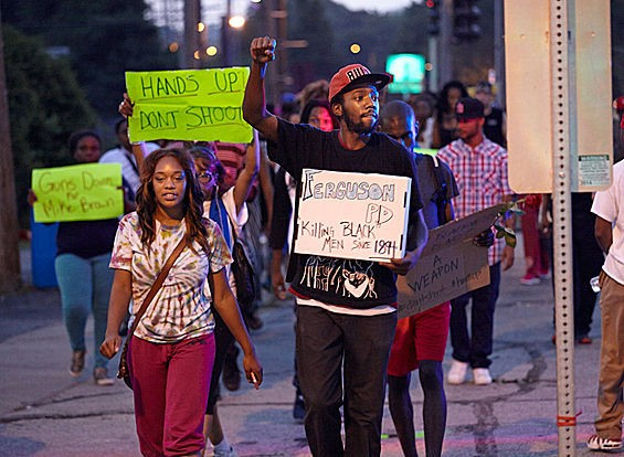Protesters march in Ferguson on August 18. - STEVE TRUESDELL