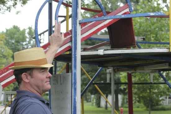 David Kechnor rests his arm against the jungle gym in the front yard of his childhood home in Tipton, MO. David's father built this jungle gym from scrap metal and the floor of an old tree fort. - DANNY WICENTOWSKI