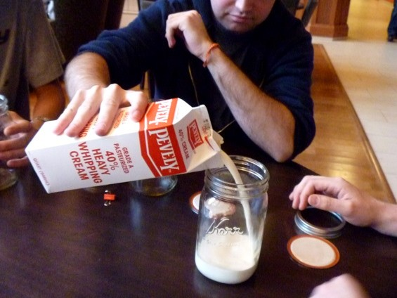Jeremy Winer pours the unchurned cream into Mason jars.