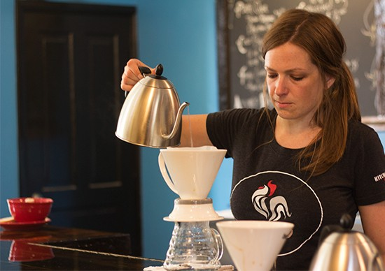 A barista works on a pour-over coffee.