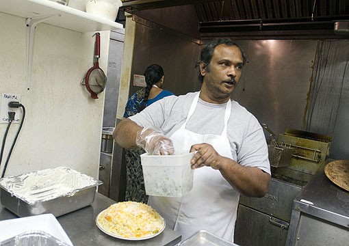Chef Venkateshwarlu specializes in south Indian cuisine. Here he is building a dum biryani from the dinner menu. The dum biryani is basmati rice cooked with special sauce and served with raita, curry sauce. See photo slideshow from Mayuri. - PHOTO: JENNIFER SILVERBERG
