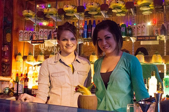 A couple of bartenders finish up a cocktail in a coconut-shaped cup.
