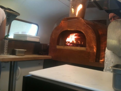 Chef Erik Jacobs peeks from behind Wanderlust Pizza's wood-fired oven inside an Airstream trailer. - ROBIN WHEELER