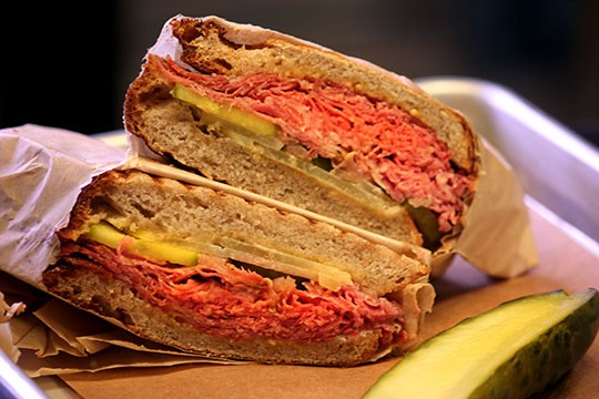 The pastrami sandwich features rye bread, pastrami, kickapoo cheese, mustard, onions and pickles. - KAITLIN STEINBERG