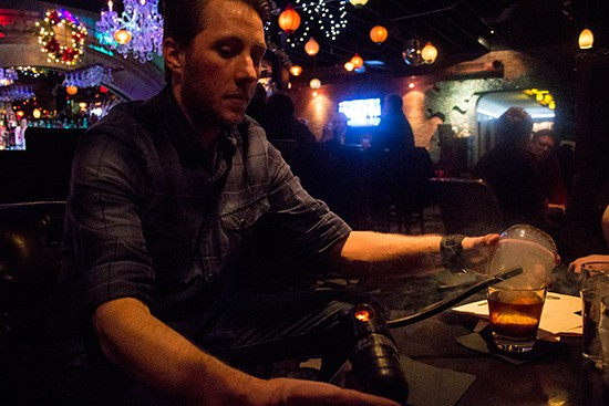 """Bartender Terry Oliver infuses a bourbon-based """"smoke wagon"""" cocktail with French-plum tea smoke at the table."""