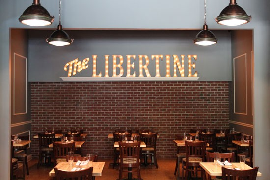A large illuminated sign anchors the dining room at The Libertine. | Evan C. Jones