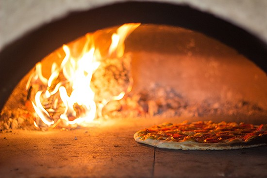 The oven bakes pizzas at a smoldering 850 degrees.