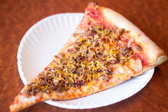 A slice of bacon-cheeseburger pizza.