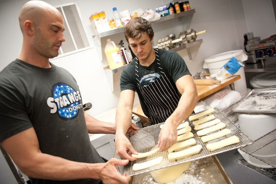 Jason Bockman, left, and Tyler Fenwick, right, work in the kitchen as patrons begin lining up outside Strange Donuts. - JON GITCHOFF