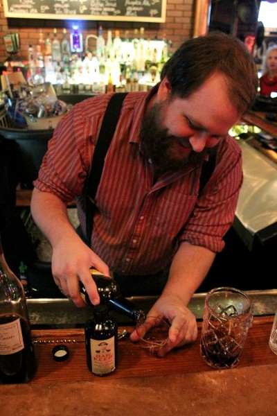 Danno's bartender Jon Hellwig pours a shot for his holiday cocktail. - MABEL SUEN