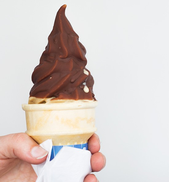 Chocolate-dipped soft serve in a cake cone.