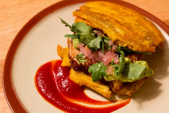 "El Jibarito, a fried plantain ""sandwich"" with pork belly, tomato-chipotle jam, avocado and pickled red onion. - MABEL SUEN"