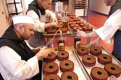 The monks inject rum into a batch of fruitcakes. - IMAGE VIA