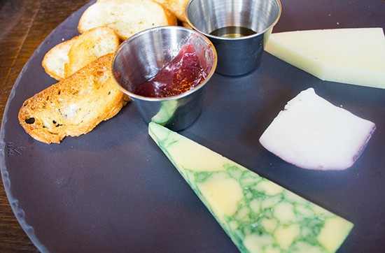 Cheese plate with local honey, fruit jam and crostini.