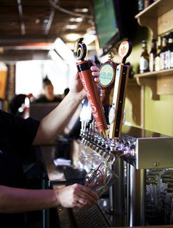 PW Pizza bartender Renee Ludwig pours a pint from local Six Row Brewing. - JENNIFER SILVERBERG