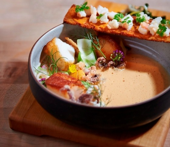 Eel and uni bouillabaisse with cauliflower puree, uni bottarga, pickled shrimp and rouille crostini with backyard kale. | Greg Rannells