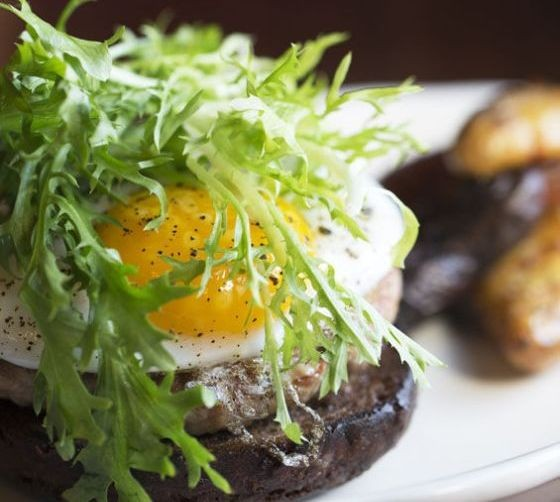 Duck Burger with remoulade, prairie breeze Irish cheddar, mixed greens, onion jam, and a duck egg on a challah bun with french fries. | Jennifer Silverberg