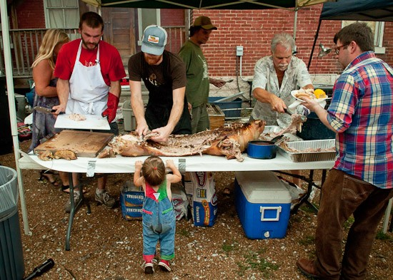 """Brad """"Mort"""" Munger (left) and John Joern (right) carve the first of two roasted pigs at the Off Broadway Pig Roast on Sunday. - BRIAN HEFFERNAN"""