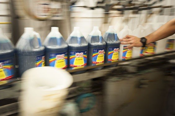 Ryan Caselton keeps bottles of blueberry moving at downtown's Rio Syrup Company. - PHOTO BY KHOLOOD EID