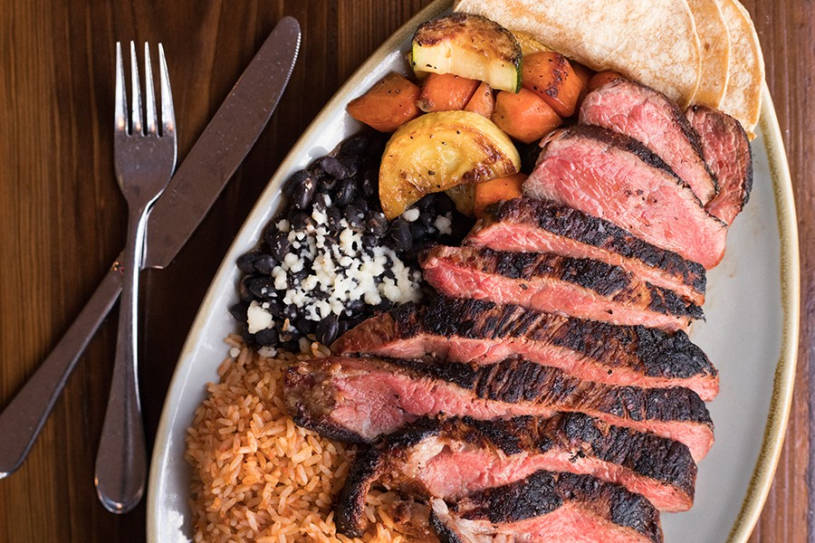 The ribeye, a highlight of Barrio's menu, has a wonderfully seasoned exterior and is served with rice and beans. - MABEL SUEN